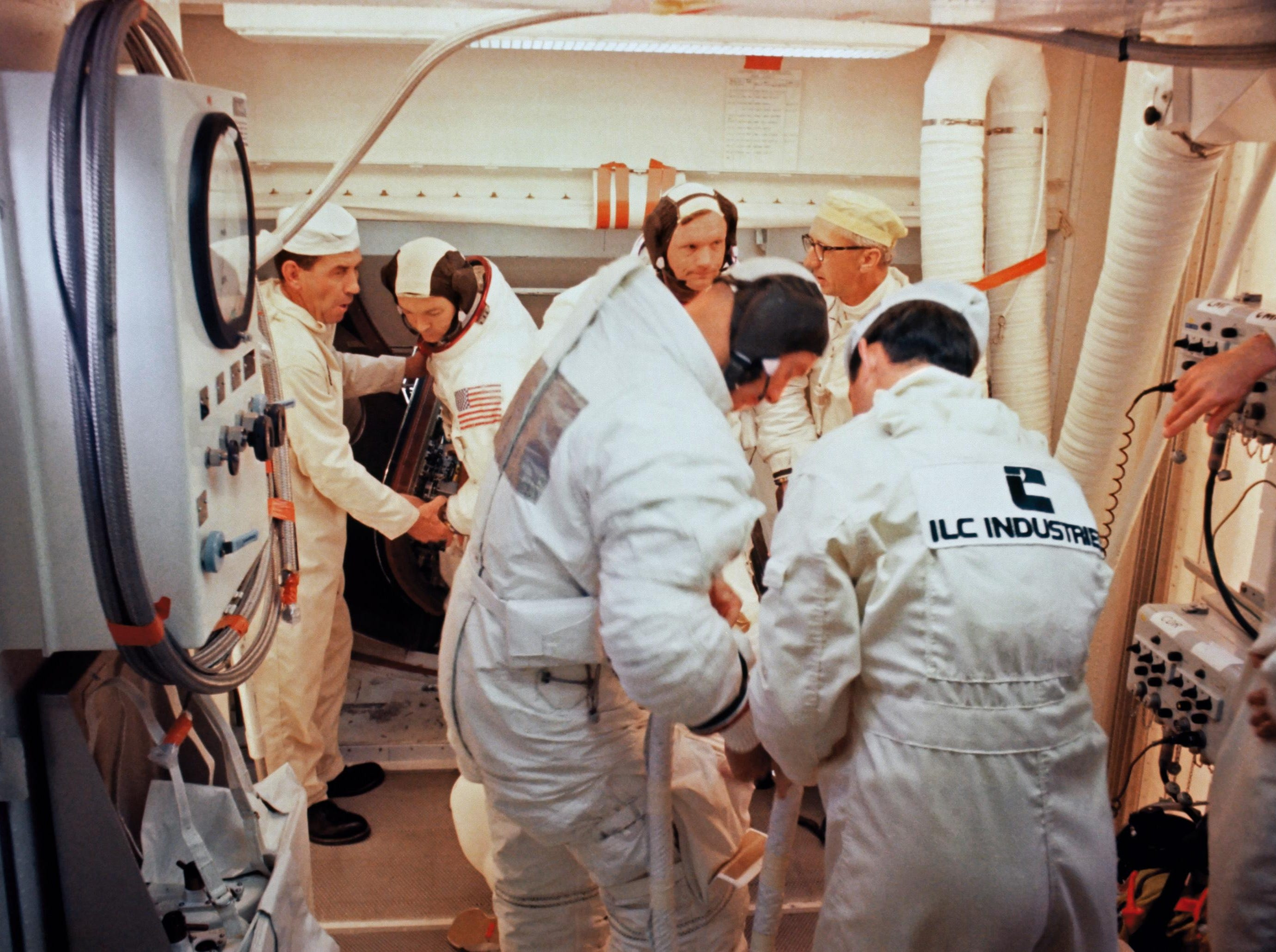 Within the White Room atop the gantry on Launch Complex 39 Pad A, the Apollo 11 astronauts Pad leader Guenter Wendt talks with Neil Armstrong. Astronaut Michael Collins is to the left of Armstrong.