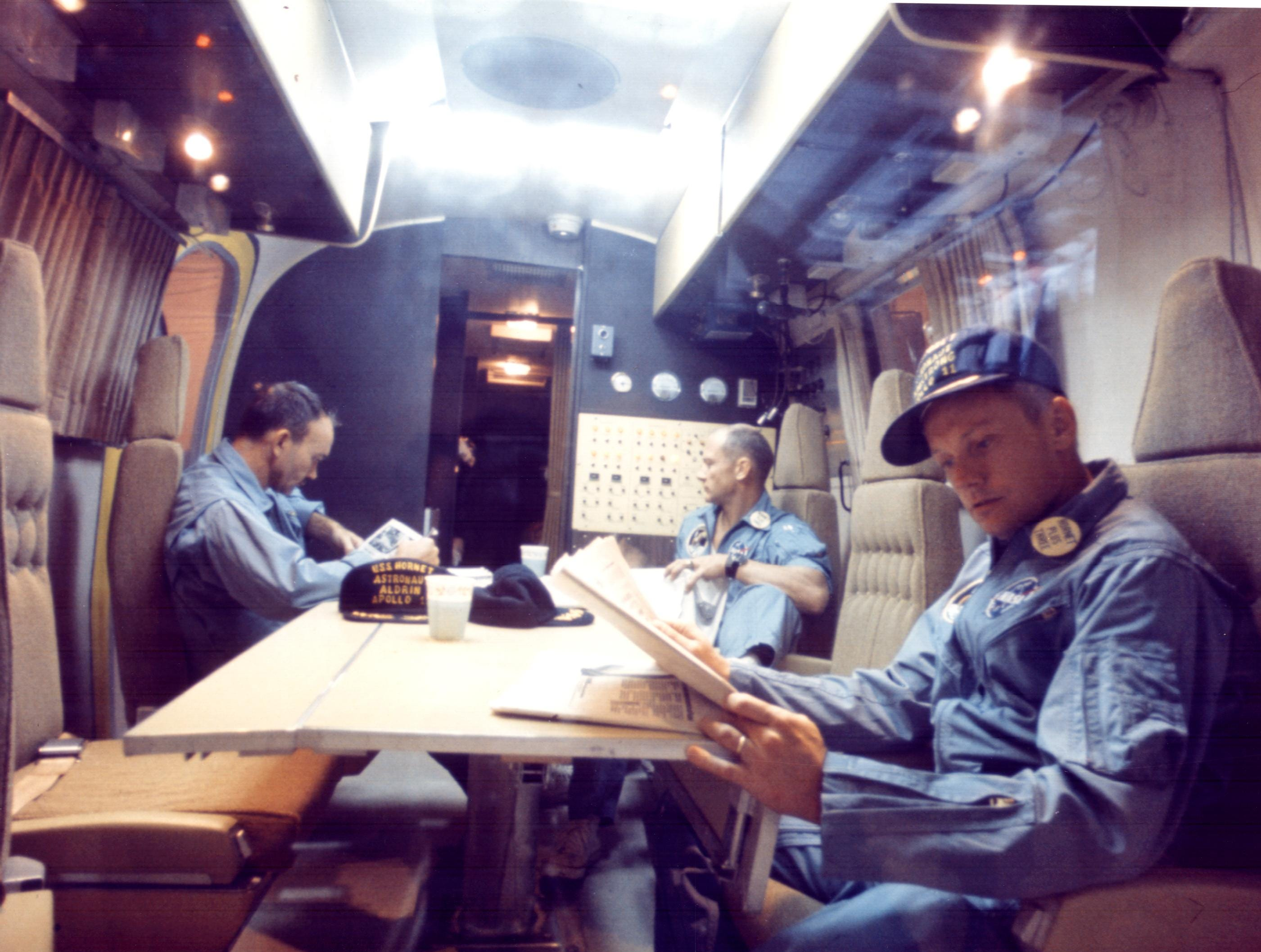 Within the Mobile Quarantine Facility, Apollo 11 astronauts (left to right) Michael Collins, Edwin E. Aldrin Jr. and Neil A. Armstrong relax following their successful lunar landing mission.