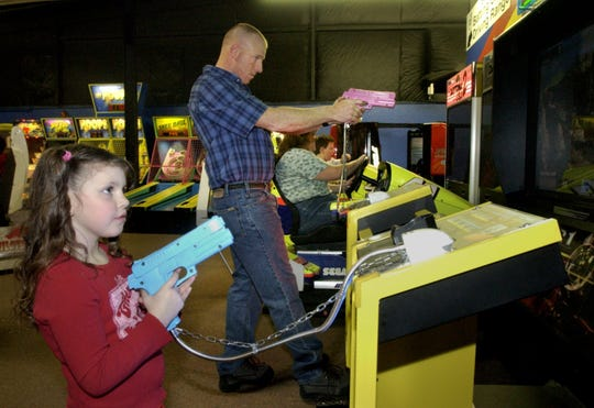 Sgt. 1st Class Matt Titus of Hinesburg, center, uses some of his marksmanship skills as he plays a video game with his daughter, Mary, 5, as the rest of his family tries different attractions at Pizza Putt in South Burlington in 2005.