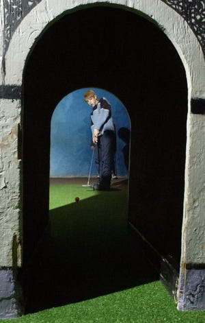 Sam Kleh, 12, of Colchester putts through a replica of the Arc de Triomphe during a miniature golf tournament Thursday night at Pizza Putt in South Burlington in 2004.