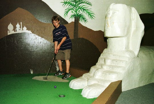 Nick Brice, 14, of South Burlington is surrounded by Egyptian scenery as he plays miniature golf at Pizza Putt in 1999.