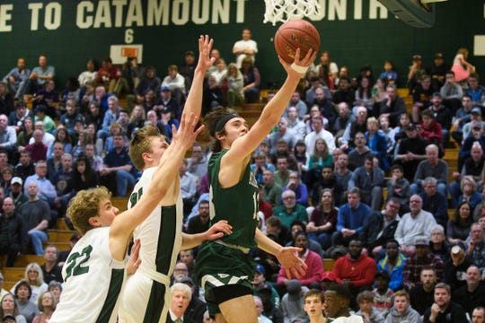 St. Johnsbury's Alex Carlisle (13) leaps for a lay up during the boys DI semifinal basketball game between the St. Johnsbury Hilltoppers and the Rice Green Knights at Patrick Gym on Monday night March 11, 2019 in Burlington, Vermont.