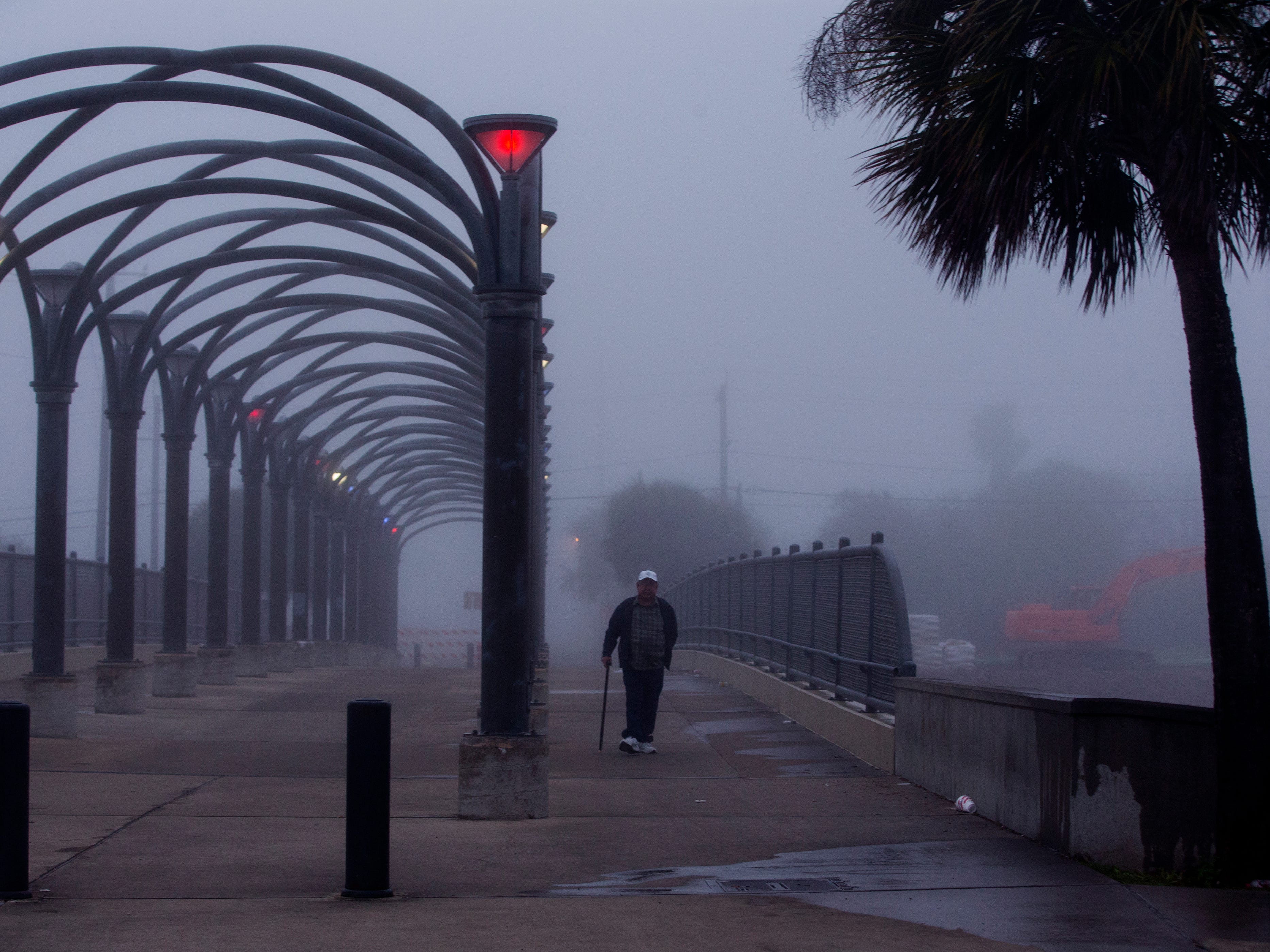 A man crosses over Interstate-37 on a pedestrian bridge on Monday, March 11, 2019. Heavy fog rolled through the area.