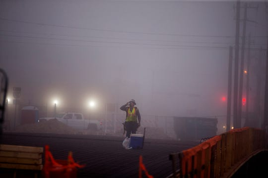 Construction workers work on the Staples Street Bridge over Interstate-37 in heavy fog on Monday, March 11, 2019.