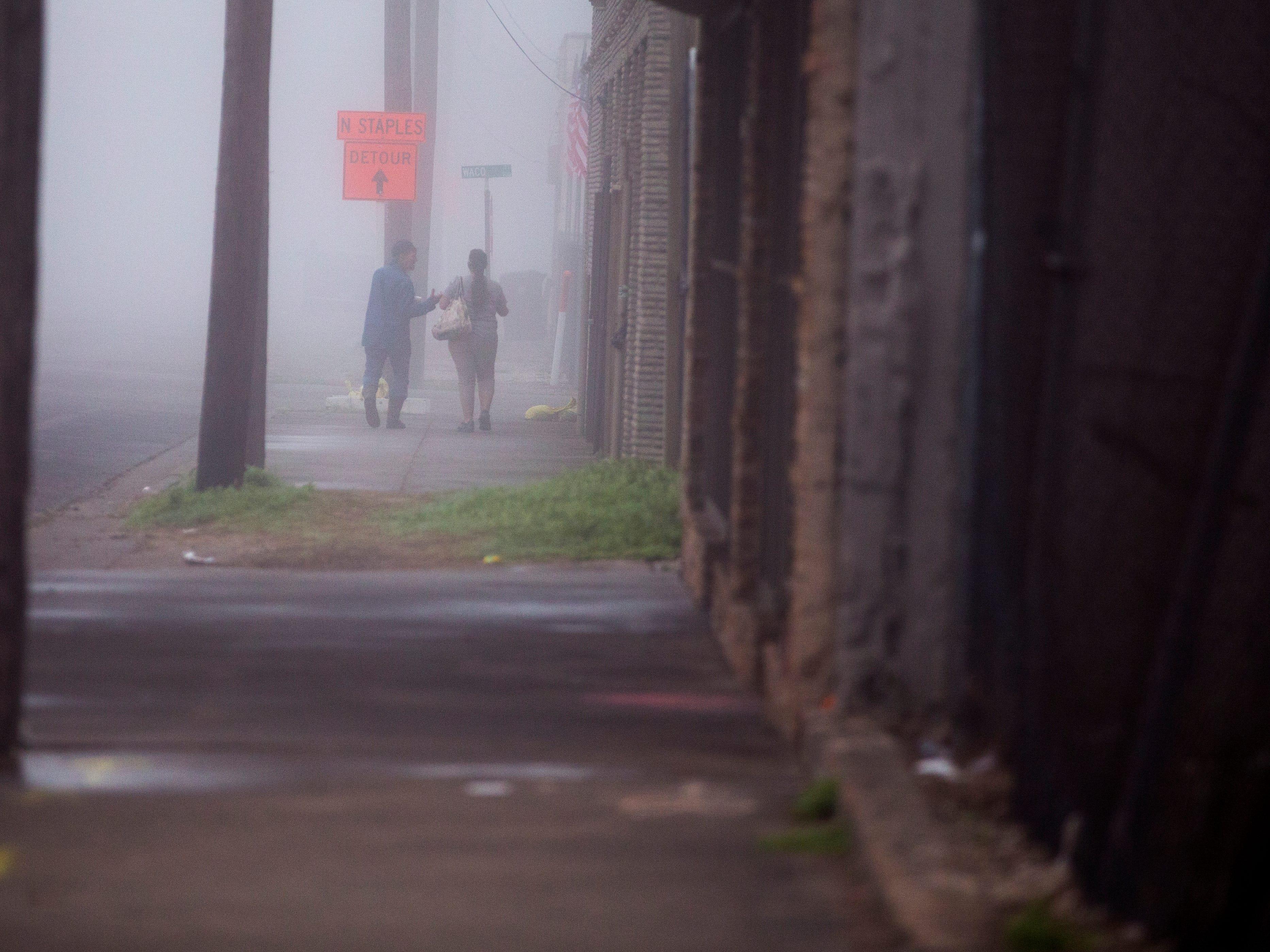 People walk along Antelope Street in heavy fog on Monday, March 11, 2019.