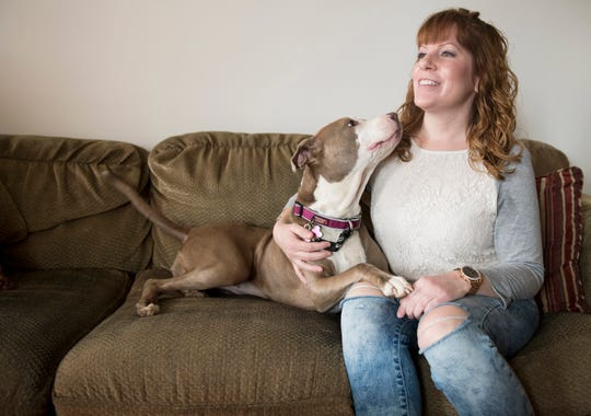 Julie Watson-Daly, an analyst and published poet, sits with her dog, Skyy, in their Deptford home. Watson-Daly survived endometriosis, a common but little understood condition that causes debilitating periods and compromises fertility.