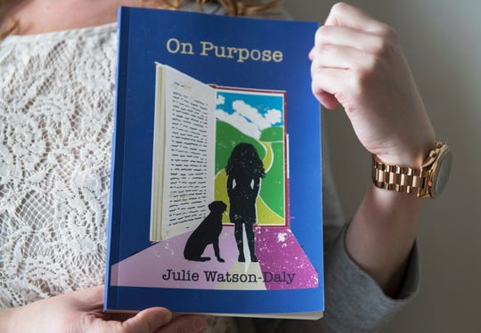 Julie Watson-Daly, an analyst and published poet, holds a copy of her book as she stands in her Deptford home. Watson-Daly suffered from extreme symptoms from age 12 until she had a complete hysterectomy at age 34.