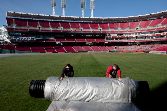 Cincinnati Reds grounds crew remove a growth cover from the field on Monday, March 11, 2019, at Great American Ballpark in Cincinnati in preparation for Opening Day.