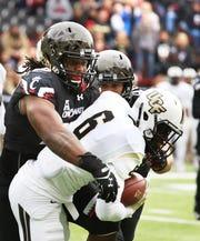 University of Cincinnati's Kevin Mouhon tackles University of Central Florida's Tristan Payton at Nippert Stadium Saturday October 31, 2015.