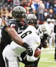 University of Cincinnati's Kevin Mouhon tackles University of Central Florida's Tristan Payton at Nippert Stadium Saturday October 31, 2015.