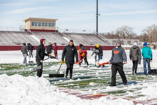 Members of the Ankeny Hawks boys' soccer team cleared snow from their field over the weekend.
