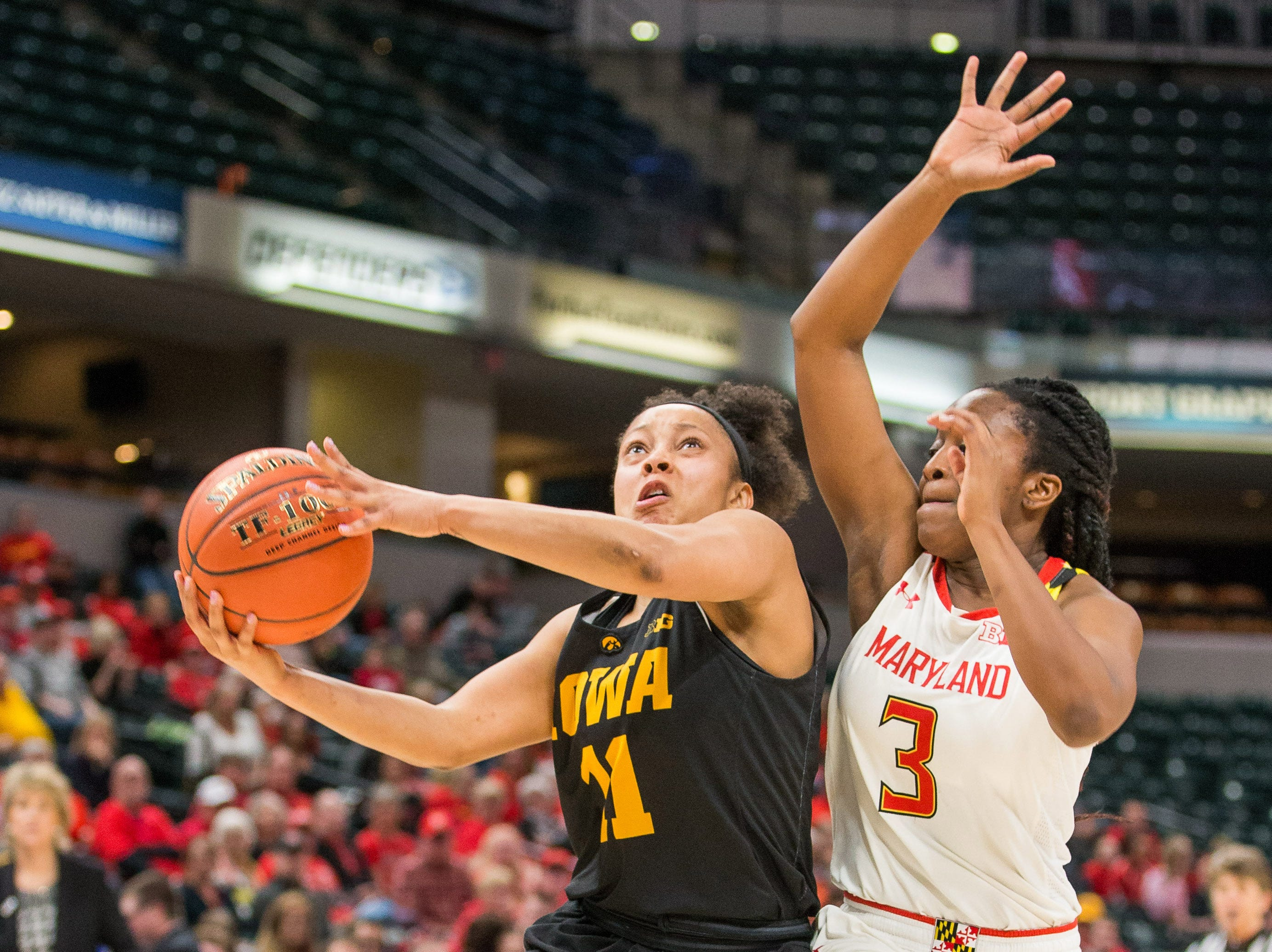 Iowa Hawkeyes guard Tania Davis (11) shoots the ball while Maryland Terrapins guard Channise Lewis (3) defends in the second half in the women's Big Ten Conference Tournament at Bankers Life Fieldhouse.