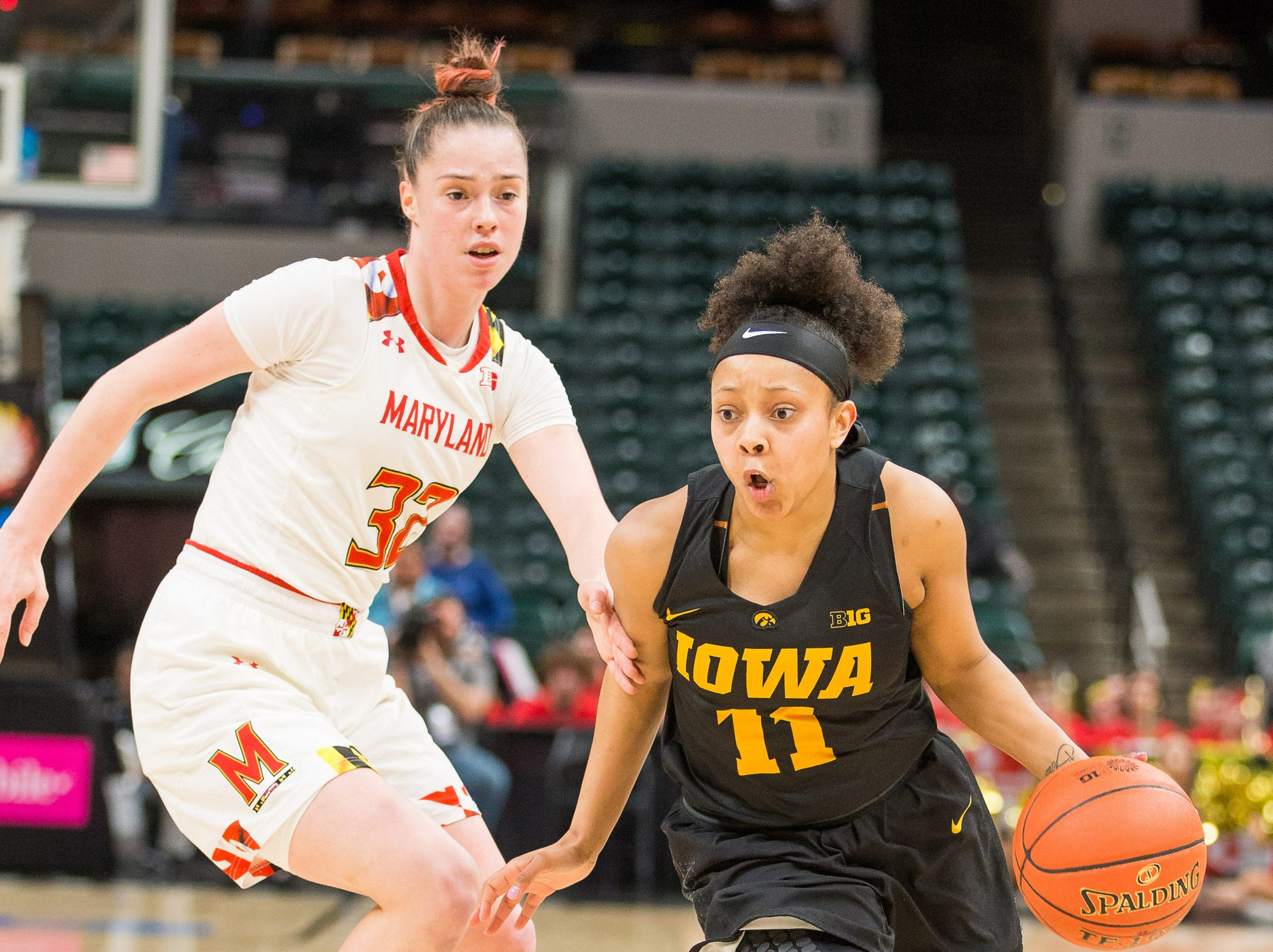 Iowa Hawkeyes guard Tania Davis (11) dribbles the ball while Maryland Terrapins guard Sara Vujacic (32) defends in the second half in the women's Big Ten Conference Tournament at Bankers Life Fieldhouse.