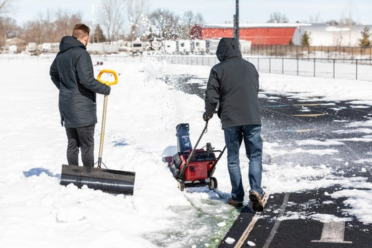 Ankeny High School boys' soccer team members clear snow from the turf on the field Sunday.
