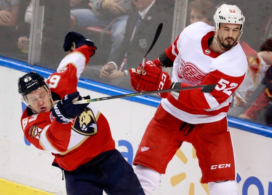 Florida Panthers right wing Evgenii Dadonov (63) and Detroit Red Wings defenseman Jonathan Ericsson (52) battle for the puck during the second period of an NHL hockey game, Sunday, March 10, 2019 in Sunrise, Fla. The Panthers defeated the Red Wings 6-1.