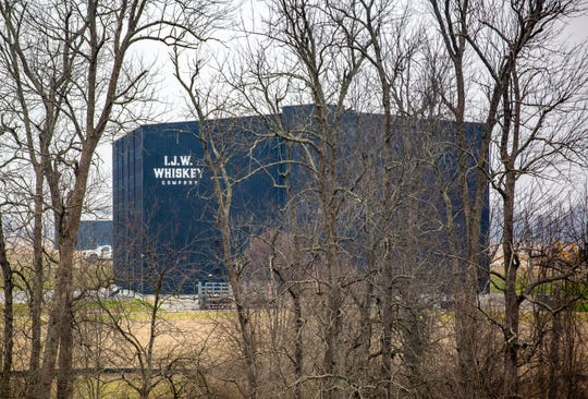 An IJW Whiskey rickhouse is seen through the trees from Lebanon Road in Danville, Kentucky, in February, 2019.