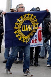 Bruce Nicholas, a 42-year General Motors employee, holds up a UAW sign during a protest outside the plant, Wednesday, March 6, 2019, in Lordstown, Ohio. General Motors' sprawling Lordstown assembly plant near Youngstown is ending production of the Chevrolet Cruze sedan, ending for now more than 50 years of auto manufacturing at the site.