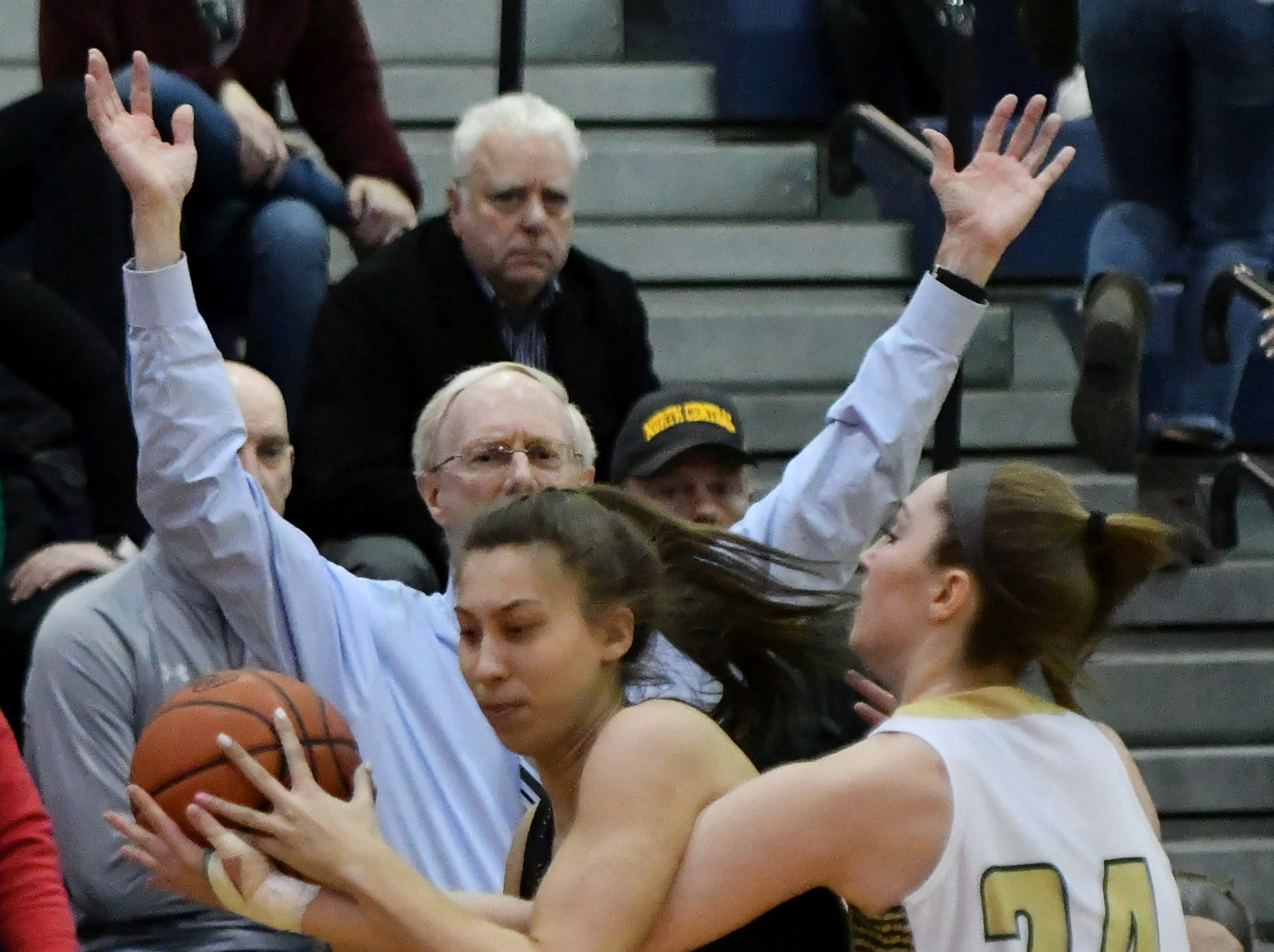 Grosse Pointe North's Regan Sliwinski (24) guards Marian's Sara Sylvester in front of Grosse Pointe North head coach Gary Bennett in the first half.