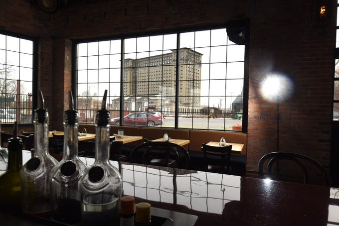 The Michigan Central Train Station is framed by the window of dining area and bar inside the Cork & Gabel restaurant.