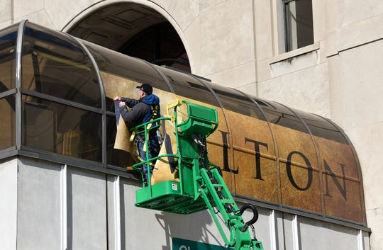 Ronald Justice, installer for Faro Imaging in Canton, installs a 'Hamilton' banner on the west side skywalk connecting to the Fisher Theatre last month.