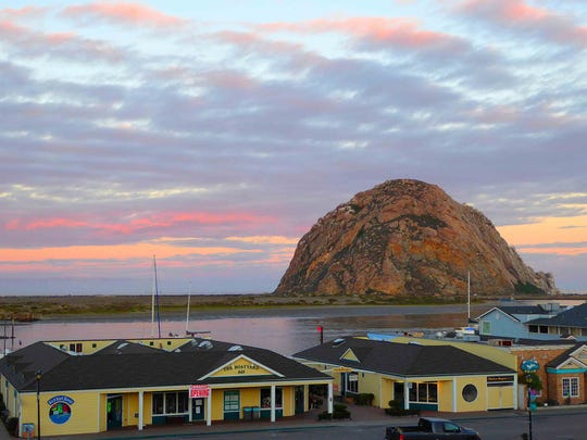 Morro Rock stands silgouetted against the reflected colors of the dawn sky. (Patricia Harris/TNS)