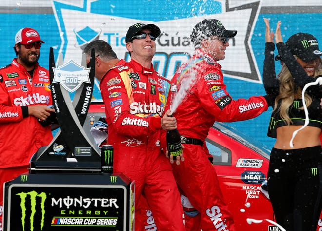 Kyle Busch sprays champagne in victory lane after winning the NASCAR Cup Series auto race at ISM Raceway in Avondale, Ariz.