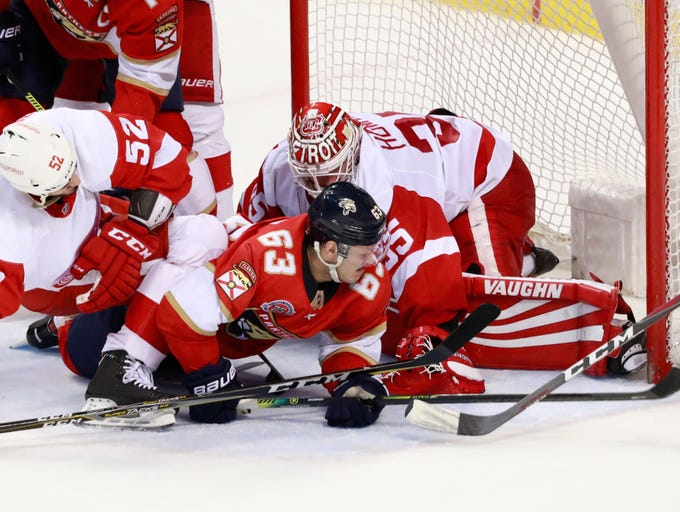 Florida Panthers right wing Evgenii Dadonov (63) attempts to shoot past Detroit Red Wings goaltender Jimmy Howard (35) and defenseman Jonathan Ericsson (52) during the second period of an NHL hockey game, Sunday, March 10, 2019 in Sunrise, Fla. The Panthers defeated the Red Wings 6-1. (AP Photo/Wilfredo Lee)
