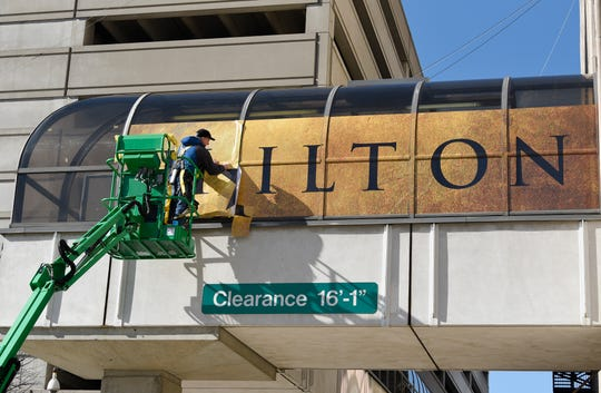 Ronald Justice, installer for Faro Imaging in Canton, installs a 'Hamilton' banner on the west side skywalk connecting to the Fisher Theatre Monday afternoon.