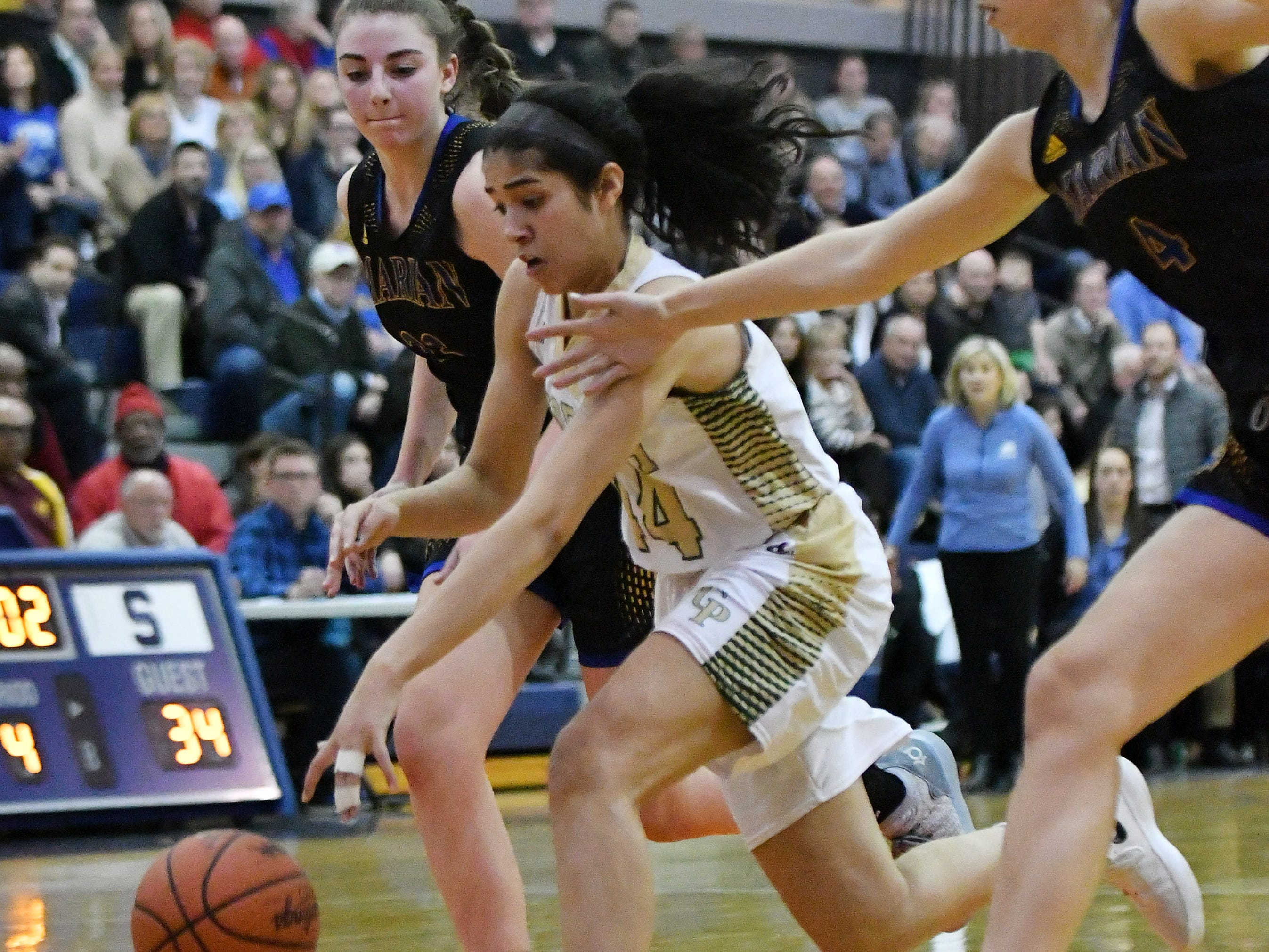 Grosse Pointe North's Christina Braker, center, dribbles through Marian's Lauren Licari, left, and Sara Sylvester in the second half.