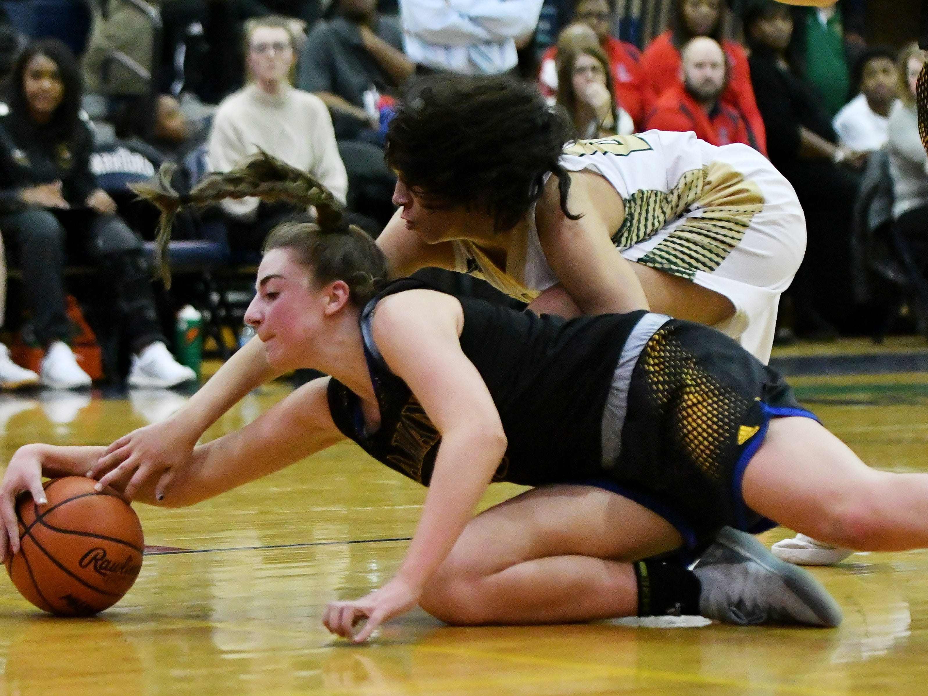 Marian's Lauren Licari and Grosse Pointe North's Christina Braker, bottom, battle for the ball in the second half.