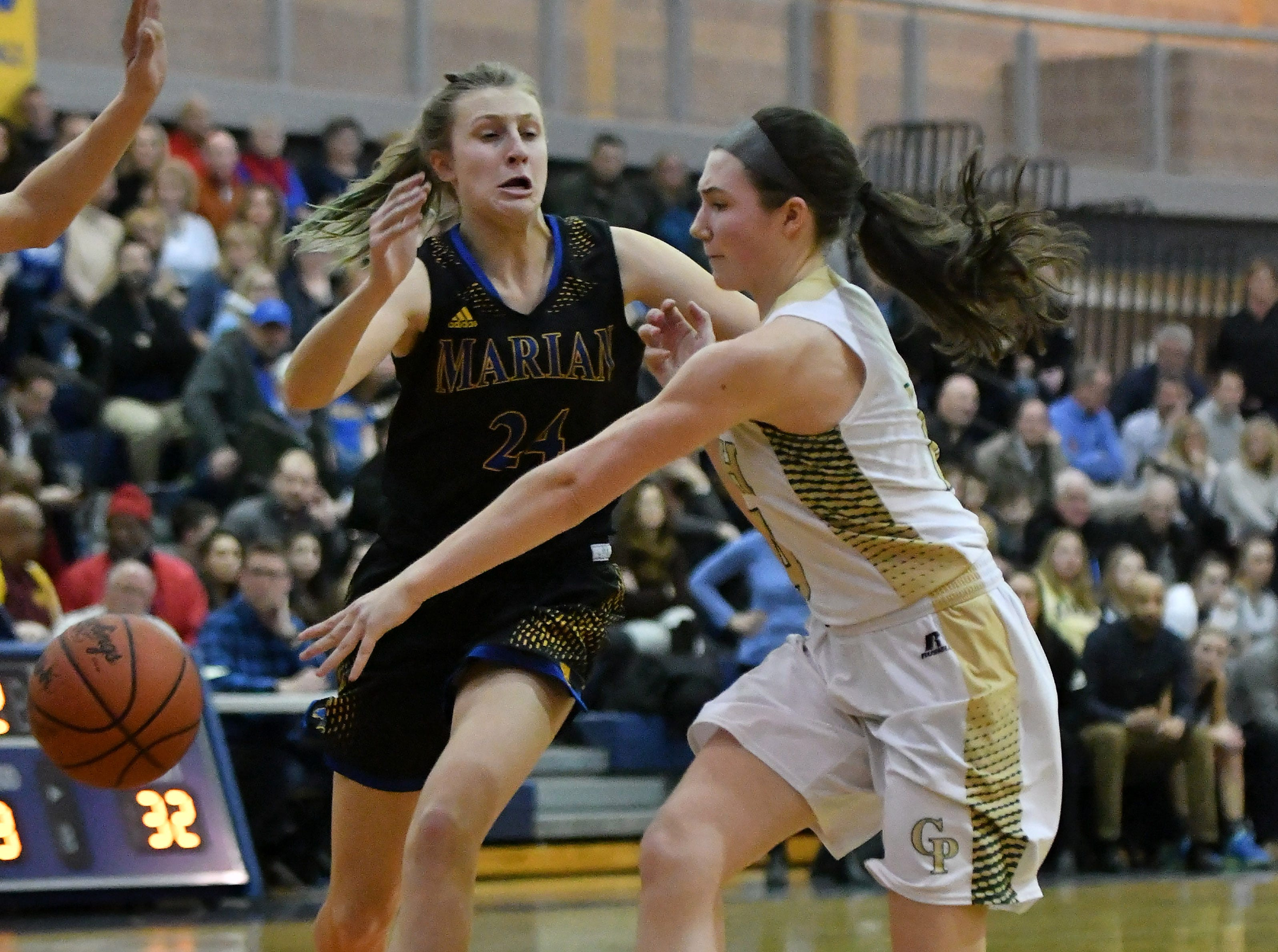 Grosse Pointe North's Maddie Kohler passes the ball past Marian's Shannon Kennedy in the second half.