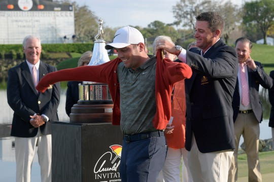 Sam Saunders, right, Arnold Palmer's grandson, helps Francesco Molinari, of Italy, put on a tournament sweater after winning the Arnold Palmer Invitational.