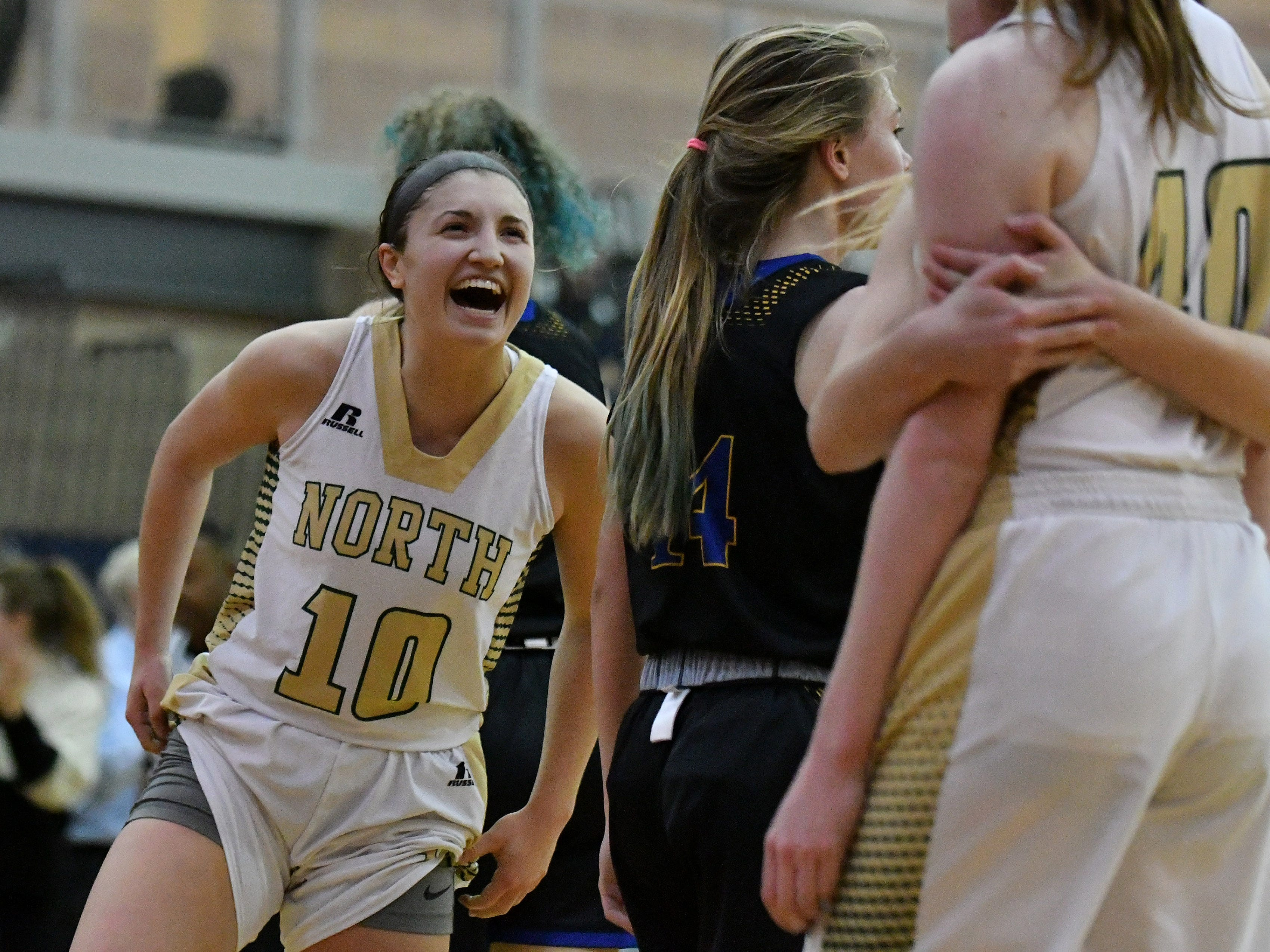 Grosse Pointe North's Evelyn Zacharias celebrates after a teammate scores in the second half of the 60-48 victory over Birmingham Marian in the regional semifinals in Southfield, Michigan on March 11, 2019.
