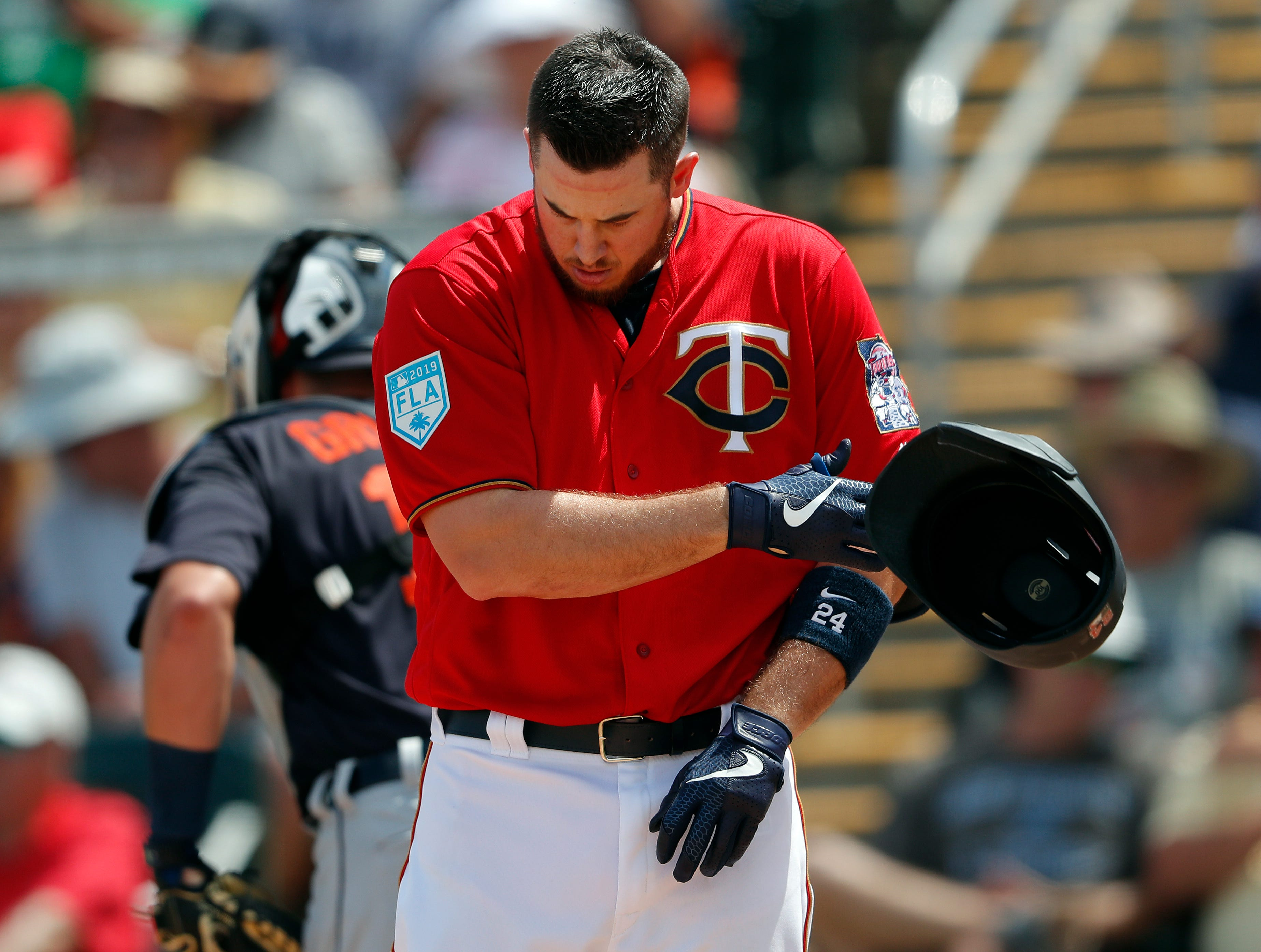 Minnesota Twins first baseman C.J. Cron (24) tosses his helmet after striking out to end the fourth inning of a spring training baseball game against the Detroit Tigers Monday, March 11, 2019, in Fort Myers, Fla.