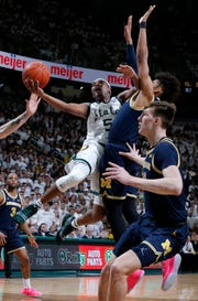 Michigan State's Cassius Winston goes to the basket against Michigan's Jordan Poole, center, and Colin Castleton, right, during the second half Saturday.