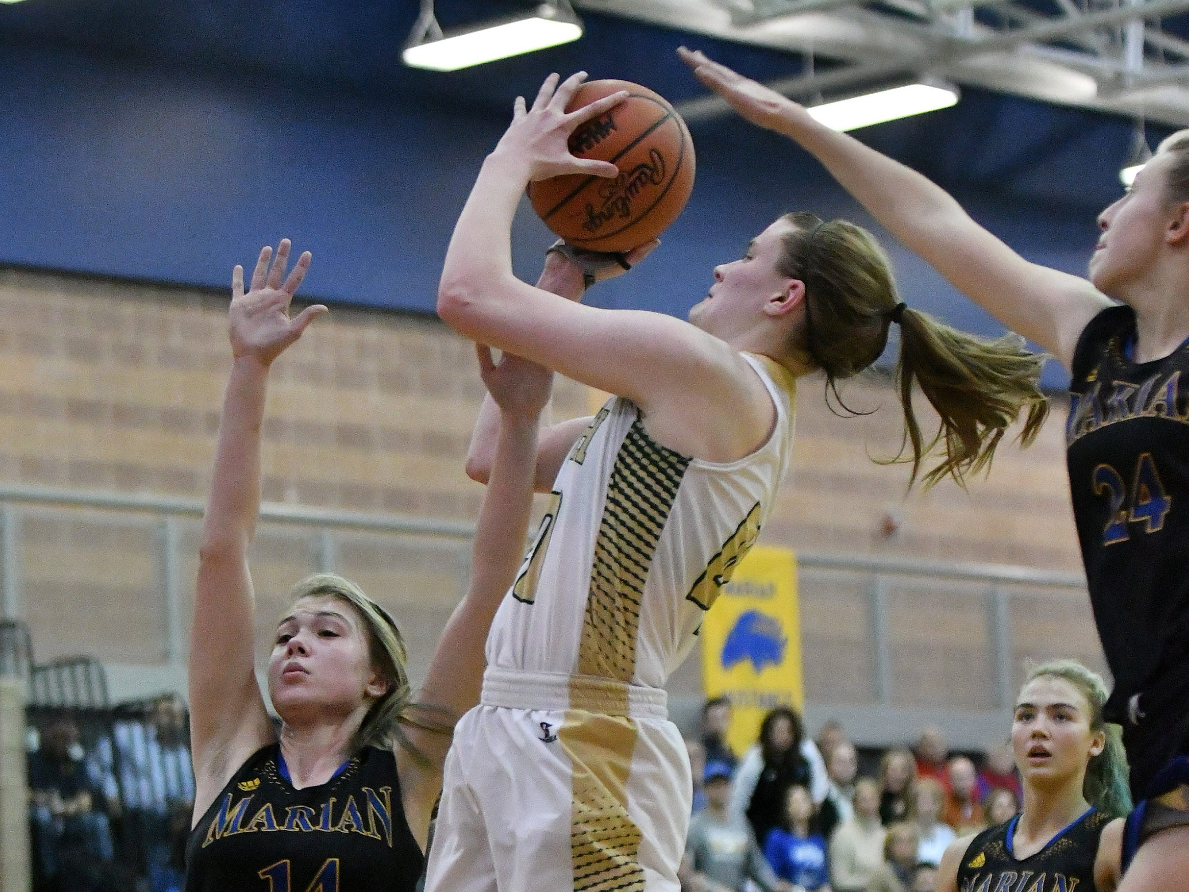 Marian's Grace Rotter (14) and Shannon Kennedy (24) defend a shot by Grosse Pointe North's  Julia Ayrault in the second half.