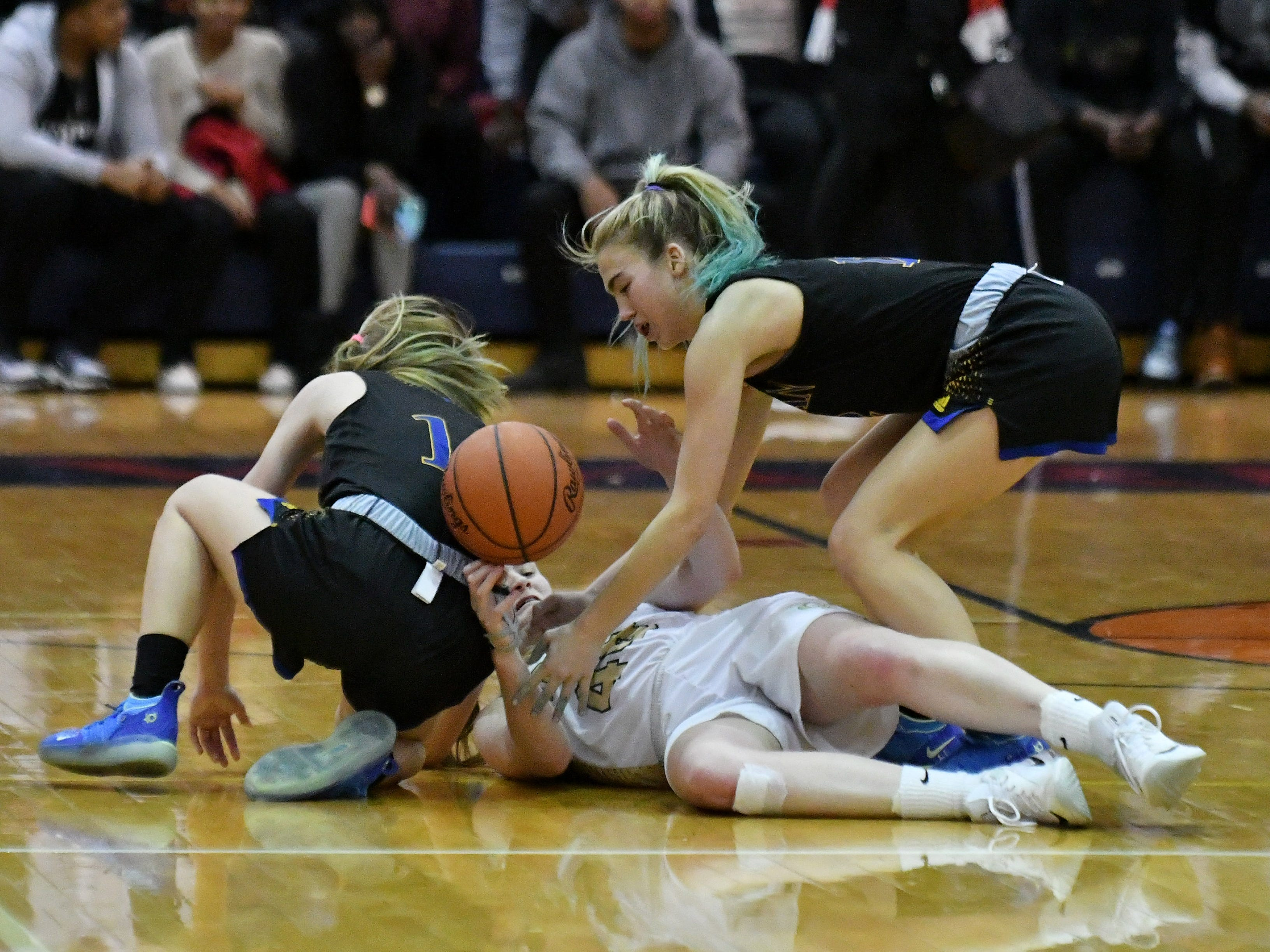 Marian's Olivia Moore, right, and Grace Rotter, left, get the ball from Grosse Pointe North's Julia Ayrault in the second half.