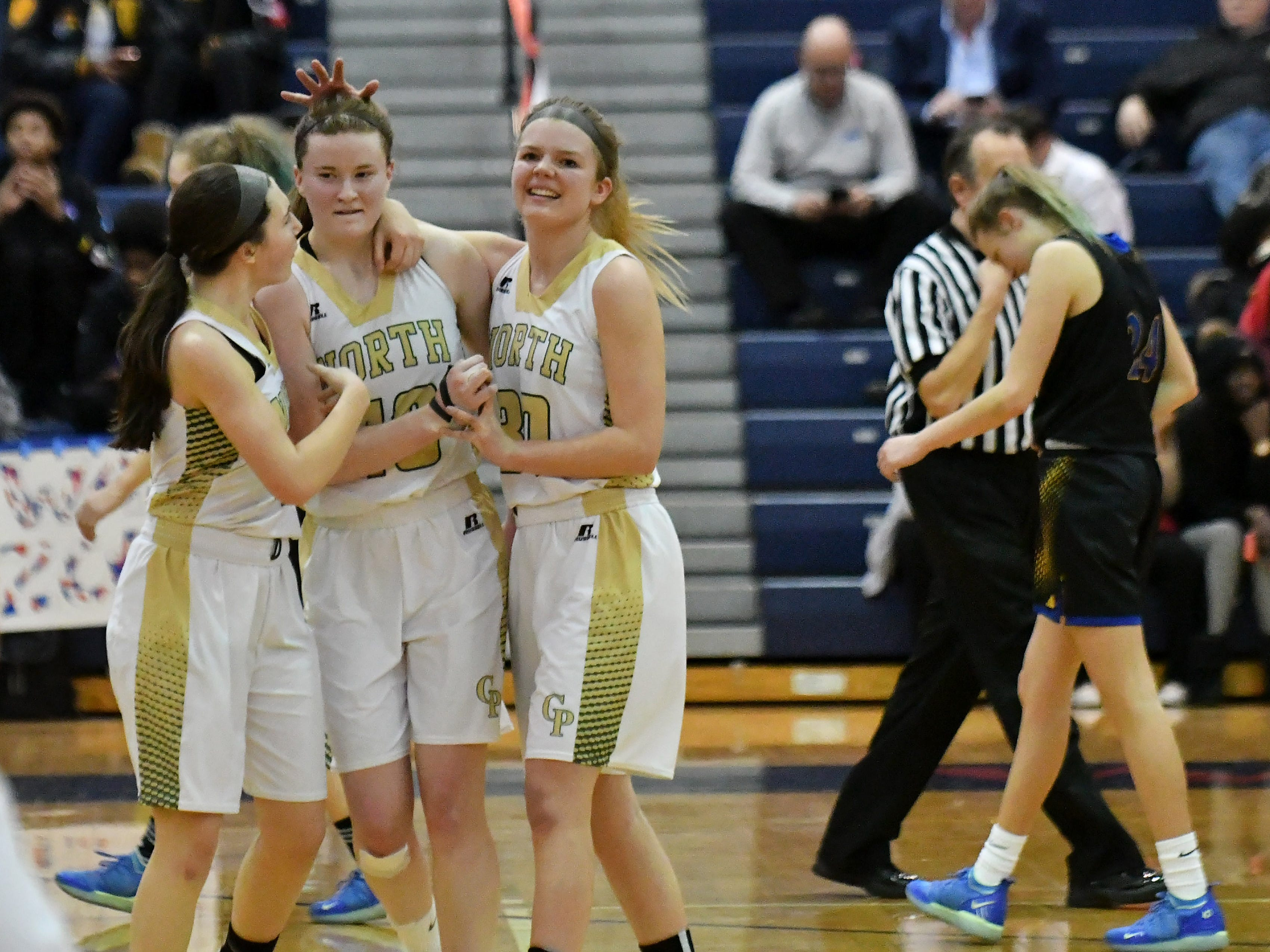 Grosse Pointe North teammates, from left, Maddie Kohler, Julia Ayrault and Maddie Mills celebrate the win.