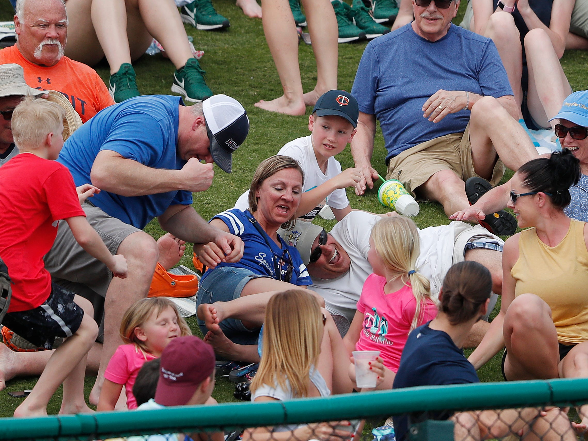 Fans sitting behind the left field fence during a spring training baseball game between Detroit Tigers and Minnesota Twins scramble for a home-run ball off the bat of Detroit Tigers left fielder JaCoby Jones Monday, March 11, 2019, in Fort Myers, Fla.