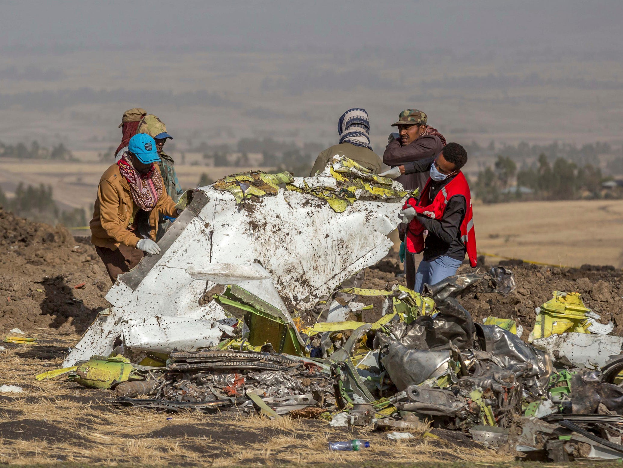 Rescuers work at the scene of an Ethiopian Airlines flight crash near Bishoftu, or Debre Zeit, south of Addis Ababa,  Ethiopia, Monday, March 11, 2019. A spokesman says Ethiopian Airlines has grounded all its Boeing 737 Max 8 aircraft as a safety precaution, following the crash of one of its planes in which 157 people were killed.