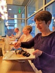 Chef Cheryl Mochau dishes up a brussels sprout appetizer from Comfort by the Cross-Eyed Cricket on an Evansville Culinary Tour.