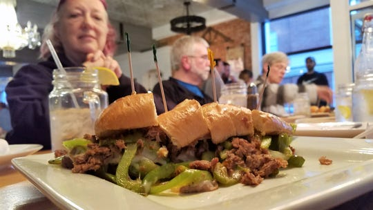 Bev Ray, left, is ready to enjoy a Philly steak sandwich at Comfort by the Cross-Eyed Cricket on an Evansville Culinary Tour.