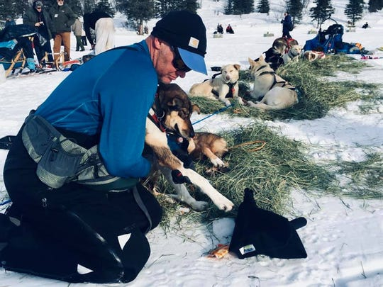 Brett Bruggeman cares for his team at a checkpoint along the route of the Iditarod in Alaska.