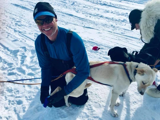 Great Falls musher Brett Bruggeman cares for one of his dogs in Alaska this week, where he is competing in the Iditarod.