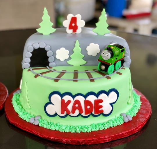 A Thomas & Friends cake topper adorns a birthday cake done by Laling's Cakes.