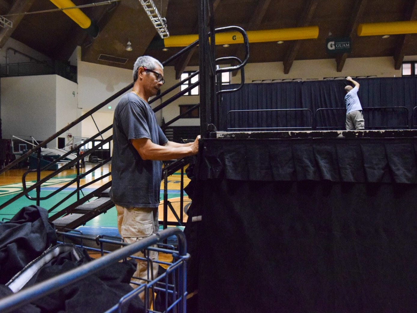 Maintenance worker Tony Guilas applies a skirt to the University of Guam Calvo Field House stage in preparation for the 51st UOG Charter Day, March 11, 2019.