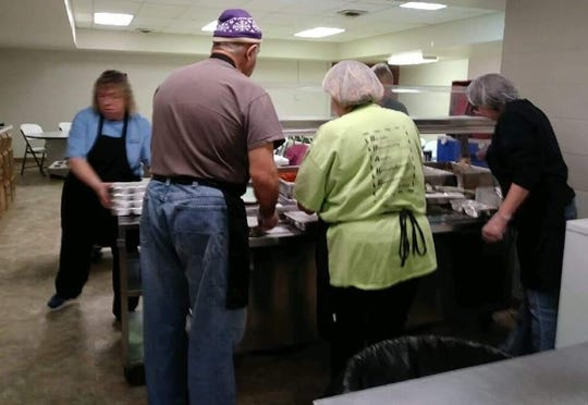 Meals on Wheels workers portion out and package meals daily at The Gathering Place senior center for local recipients.