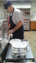 """Frank Rucks helps get """"Meals on Wheels"""" lunches ready for delivery. Roughly 90 people get a meal delivery every weekday afternoon in Henderson County, but many more are on the waiting list."""
