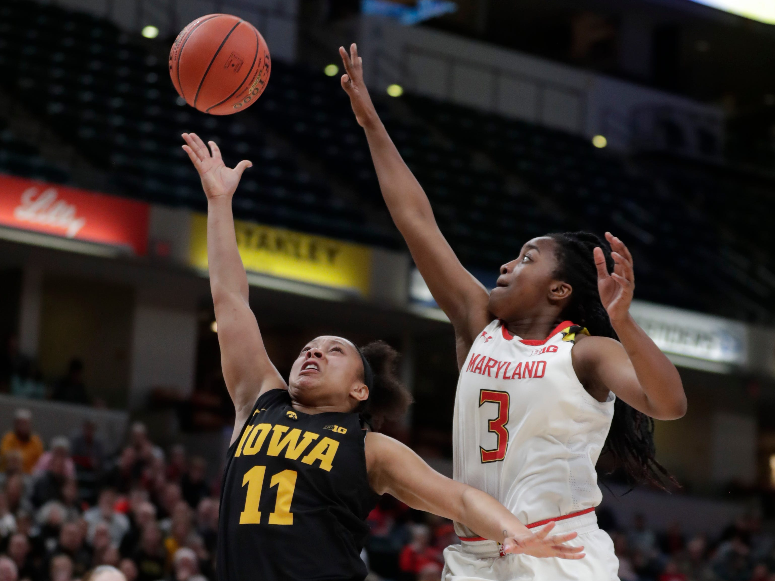 Iowa guard Tania Davis (11) shoots in front of Maryland guard Channise Lewis (3) in the second half of an NCAA college basketball championship game at the Big Ten Conference tournament in Indianapolis, Sunday, March 10, 2019. Iowa defeated Maryland 90-76.