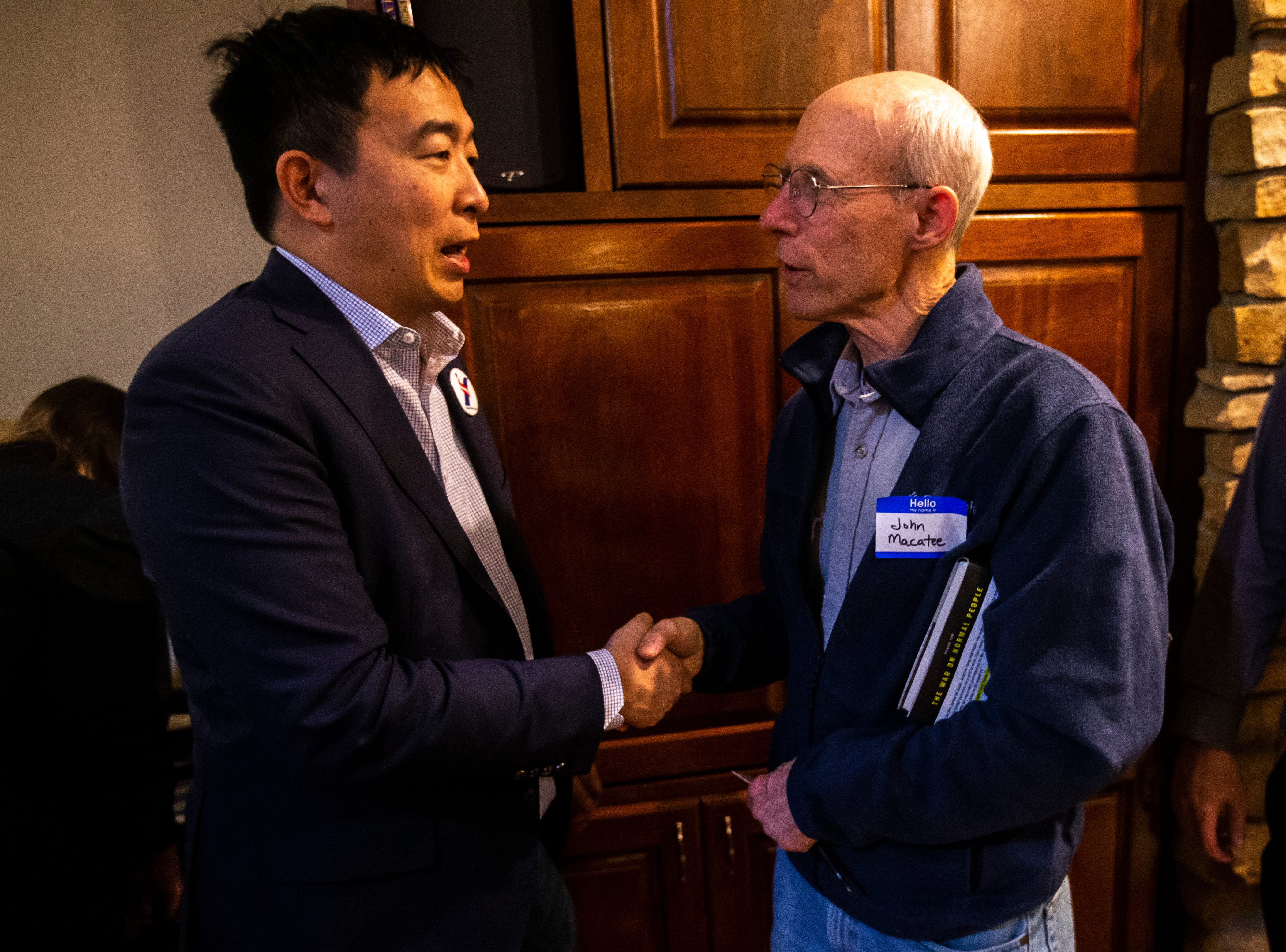 """Andrew Yang, a 2020 Democratic presidential candidate, shakes hands with John Macatee, of Iowa City, at the """"Potluck Insurgency,"""" a dinner party organized by local activists, on Sunday, March 10, 2019, at a home in Iowa City, Iowa."""